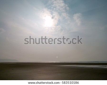 A hazy sun casts its light on a small breaking wave on the beach at Westward Ho!, North Devon, England