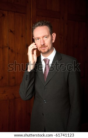 A head and shoulders businessman stood in front of some wooden panels.  He has a phone to his ear and is looking away from the camera.