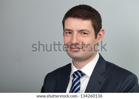 A head and shoulders shot of a 40 year old business man in a suit and shirt with blue tie.