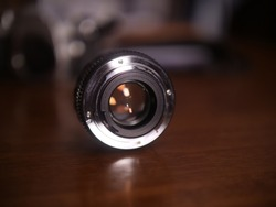 A head on view of a promaster 50 mm lens with the aperture blades wide open to f 1.8. Shallow focus on the glass that reflects, as the whole surface is exposed to capture as much light as possible