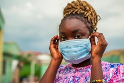 A head shot beautiful African lady wearing medical face mask for protection after covid-19 lock down or quarantine - black millennial lifestyle and corona virus pandemic