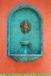 A head water fountain on red wall
