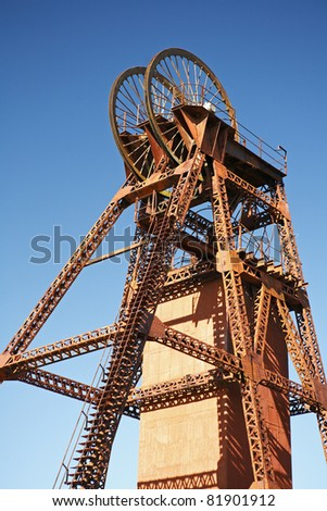 A headframe, winding tower, poppet head or pit head, is used in shaft mining to support the winding mechanism. The mine shaft is used to gain access to an underground mining facility. Australia.