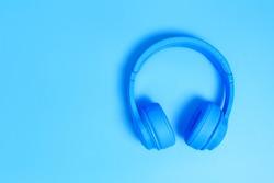 a headphones, Top view of headphones on blue background. Minimalist photo of earphones with copy space. blue dj headphones, Top view blue headphones on blue background. Above view of dj head phones.