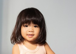 A headshot portrait of a cheerful baby Asian woman, a cute toddler little girl with adorable bangs hair, a child wearing a vest  smiling and looking to the camera.