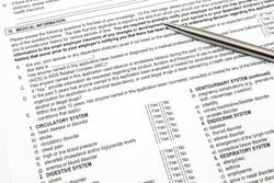A health insurance application medical information section with a pen ready to be filled out.