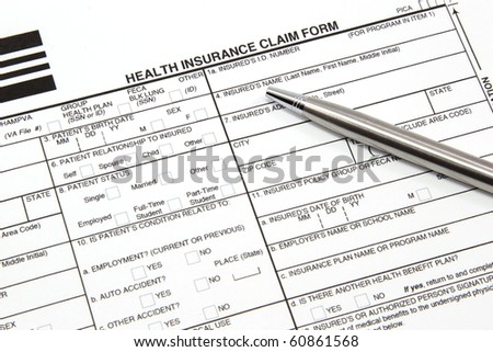 A health insurance claim form with a silver pen ready to be filled out for manual submission to an insurance carrier.