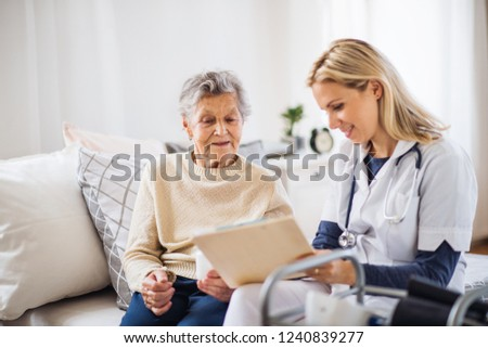 A health visitor and a senior woman sitting on a bed at home, talking.