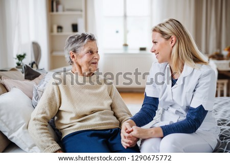 A health visitor talking to a sick senior woman sitting on bed at home.