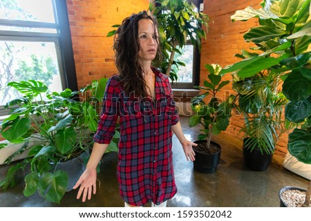 A healthy and mindful woman is seen standing by indoor plants as she practices breathing exercises to heal the sacred body chakra, with copy space