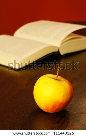A healthy apple and a open book