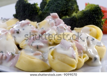 A healthy plate of tortollini with a cream sauce.