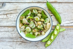 A healthy rich protein salad made from broad beans and fresh herbs. Vegetarian food.