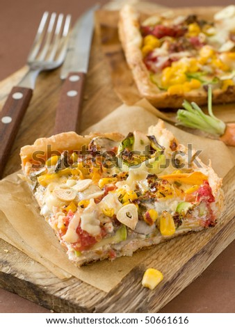 A healthy vegetarian pizza with mushrooms, tomatoes, sweet corn  and zucchini