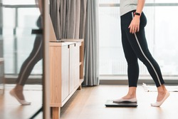 A healthy woman standing on a scale to measuring her weight in the living room after home workout in the morning. Body mass index - BMI, Hormones, Weight Loss, ideal healthy weight, Metabolism, Diet.
