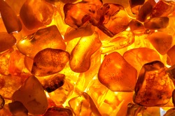 a heap of amber stones backlightet glowing