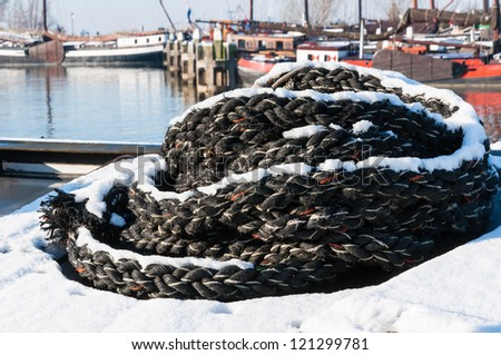 A heap of black braided rope with a layer of snow in front of some historic ships in a harbor.
