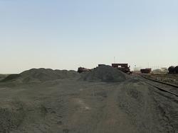 A heap of coal in a coal yard  next to a railway track