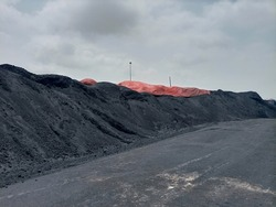 A heap of coal partially covered at a yard