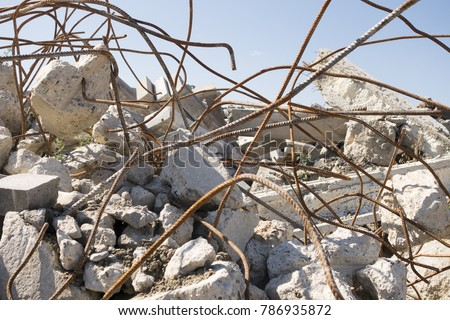 A heap of construction debris: pieces of broken concrete, curved metal rods. The remnants of broken pieces after the demolition of an old building, macro #786935872