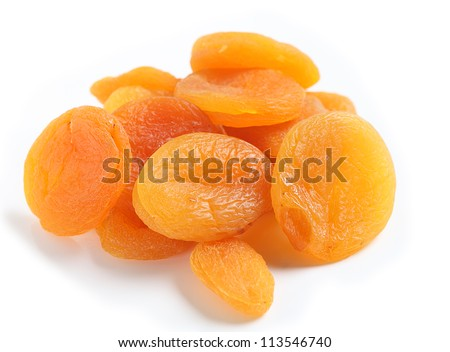A heap of dried apricots on a white background with a light shadow, viewed from above