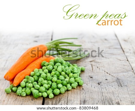 A heap of fresh green peas with carrots on it, place for your text up