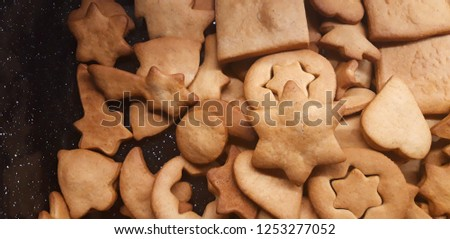A heap of freshly baked gingerbread. Lot of classic Christmas symbol shapes. Stars, hearts, bells, moons, pine trees and others. All of them is very tasty, so it is perfect element for the festive tab