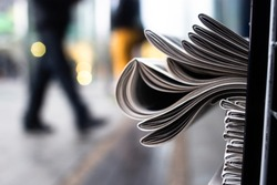 A heap of newspapers on a news stand on the background of a street