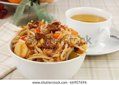 a heaping bowl of beef chow mein with a cup of hot green tea