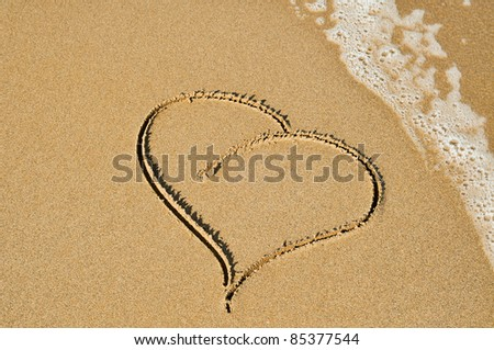 a heart carved on the sand of a beach
