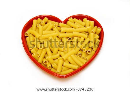 A heart dish filled with rigatoni pasta on white background.