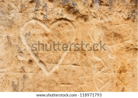 A  heart etched into the sandstone canyon walls dominates the other graffiti. - stock photo