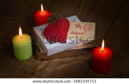 "Photo of  A heart made of red thread, gift boxes, a pine cone and a piece of paper with the words ""My beloved"" and a hand-drawn face for Valentine's Day against a background of candles or a background with boke"