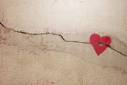 A heart painted on a cracked wall. The concept of broken heart, relationships, love, friendship, marriage, graffiti.