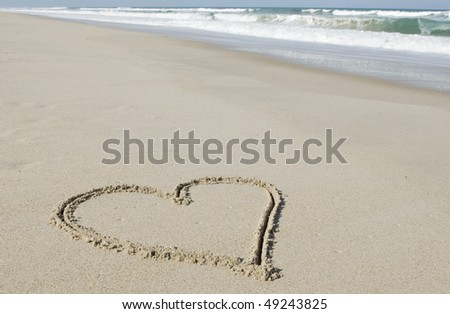 A heart shape drawn in the sand with ocean in the background, horizontal with selective focus and copy space, great for Valentine's Day