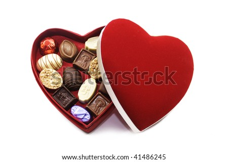 A heart shaped box of chocolates with a red felt lid. Set on an isolated white background.