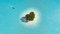 A heart-shaped paradise island in the middle of the ocean. Yacht approaching the island. Space for text