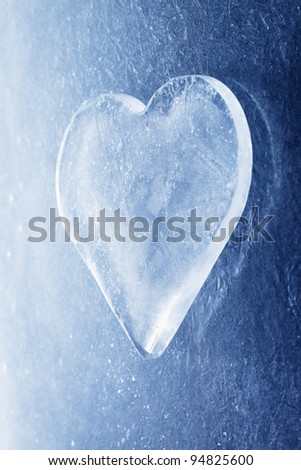 A Heart-shaped piece of ice on ice background.
