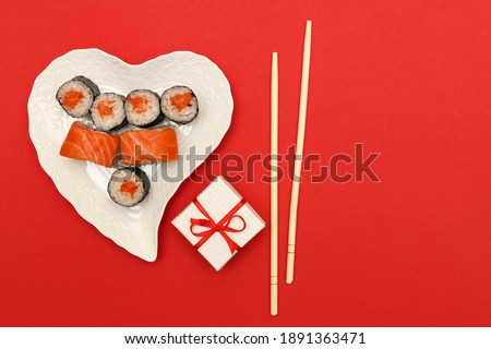 A heart-shaped plate with rolls, a gift box for jewelry and sushi sticks on a red background with space for text.Layout. Concept: romantic dinner for Valentine's Day.Fast food Stockfoto ©