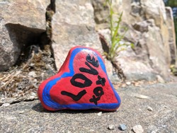 A heart shaped rock colored in red with sign love on it. Relationship, faith, love concept. Selected focus, space for copy.