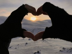 a heart shaped with hands framing the sun in the winter landscape