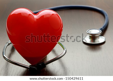 A heart with a stethoscope, isolated on wooden  background