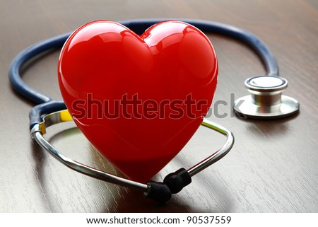 A heart with a stethoscope lying on a wooden desk
