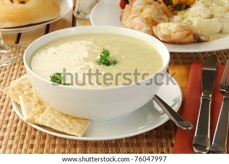 A hearty bowl of soup with fried chicken in the background