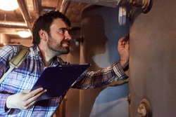 A heating fitter with a checklist checks the condensing boiler of a gas heating system