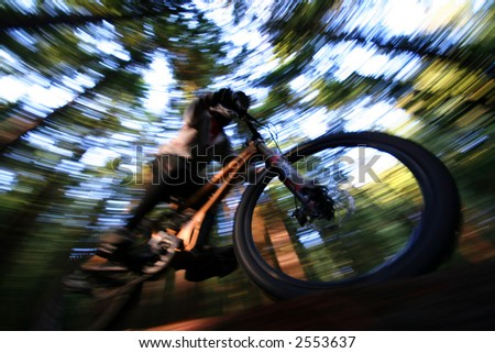 A heavily blurred mountain biker on a trail in Vancouvers famous North Shore mountains.