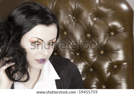 A heavily made up business woman in a leather chair - stock photo