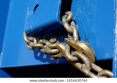A heavy duty chain secures a load on a semi truck flat bed bound for an industrial construction site.