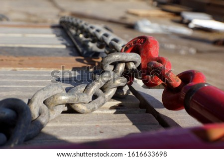 A heavy duty industrial chain secures a load of equipment to the flat bed of a truck for transportation.