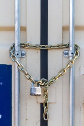 A heavy duty industrial size padlock was attached to steel chains at the entrance of an outdoor container that stores tools and equipment. Versatile image for locking, safety, security related concept